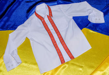 White shirt with embroidered ornament on background of the flag of Ukraine