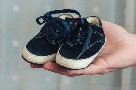 Baby shoes on parental hand. Babys bootees Stock Photo