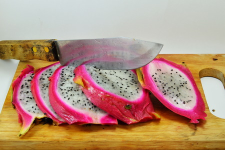 valuables: dragon fruit and knife on chopping block