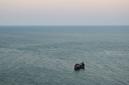 fishery: fishery boat floating on the dull sea