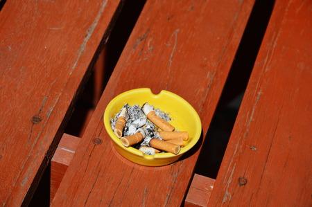 decease: yellow ashtray on wood board