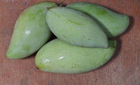 digest: green mango on the wood Stock Photo