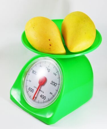 weighting: mango on weighting scale Stock Photo