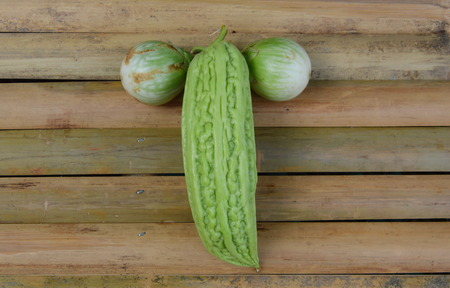 digest: bitter gourd and egg plant on bamboo desk Stock Photo