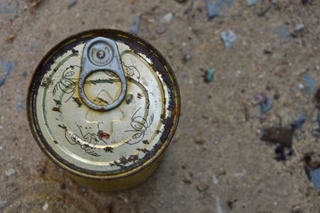 expire: rusty tin can food on the ground