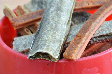 dog salmon: dog snack crispy salmon skin and chicken soft stick on bowl Stock Photo
