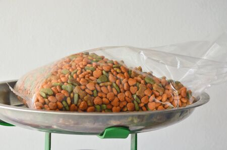 weighting: dog food in plastic bag on weighting scale tray