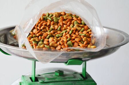 weighting: pet food in plastic bag on stainless weighting scale tray