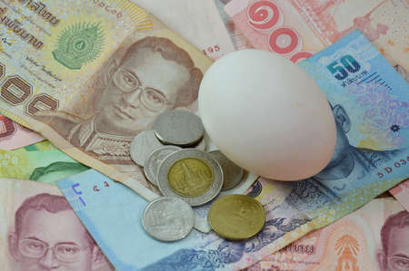 valuables: white egg with Thai banknote and coin Stock Photo