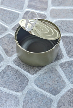 food can: empty tin food can on the tile floor
