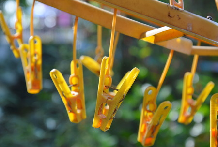 clothespin: yellow clothespin hanging on clotheline