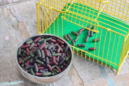 rabbit in cage: rabbit food on stainless bowl and yellow cage Stock Photo