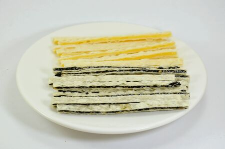 filling line: fish snack line filling black sesame and cheese on dish Stock Photo
