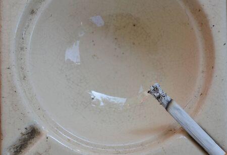 ash: cigarette on tile ash tray Stock Photo