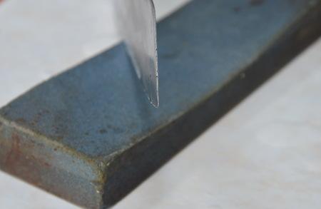 to scrape: kitchen knife blade on whetstone