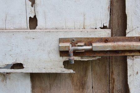 door bolt: rusty bolt on decay white wooden door Stock Photo