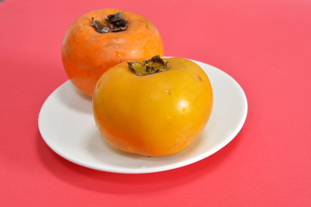 healthy economy: persimmon Chinese fruit on dish Stock Photo