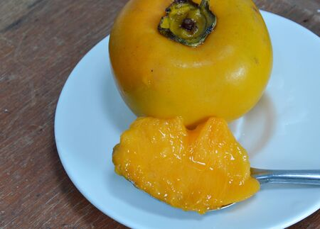 healthy economy: persimmon Chinese fruit on spoon