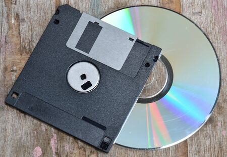 compact disc: diskette and compact disc on wood board
