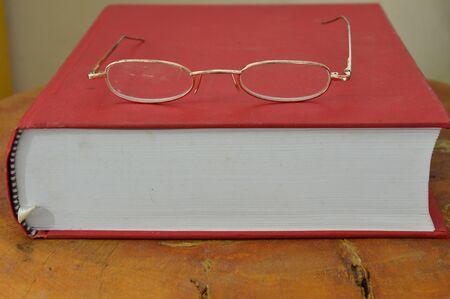 eyeglass frame: gold frame eyeglass on red book