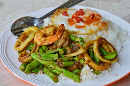fried shrimp: stir-fried curry seafood and fried egg on rice Stock Photo