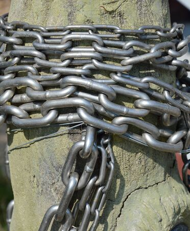 enslaved: metal chain roll over wooden pole Stock Photo