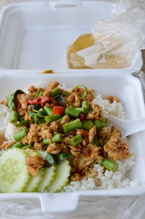 long bean: spicy stir fried chicken with basil leaf on rice in foam box for take home