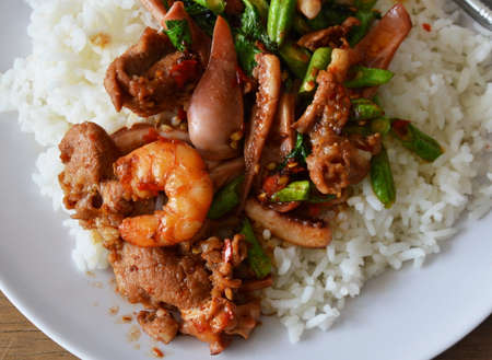 thai food: spicy stir-fried seafood with basil leaf on plain rice