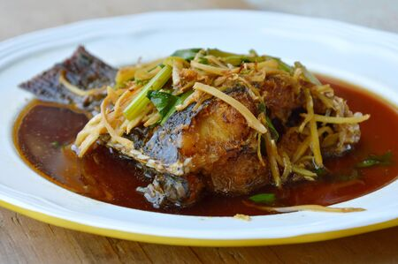 mango fish: deep fried mango fish in ginger soy sauce on dish Stock Photo
