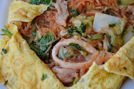 chinese noodle: stir fried sukiyaki with seafood wrapped in egg on dish