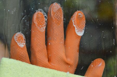 rubber glove: hand in rubber glove wipe the glass door in home Stock Photo