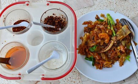 acetic acid: stir-fried noodle with seafood in black soy sauce and seasoning box Stock Photo