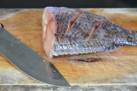 fresh water fish: fresh water fish and knife prepare for cook on wooden chop block
