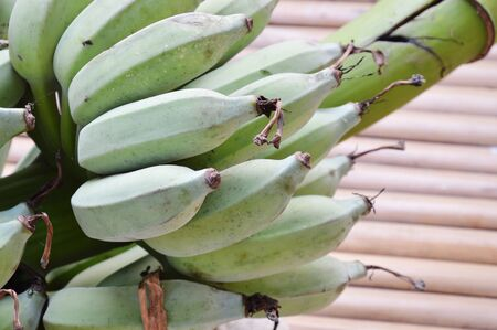 digest: bunch of raw banana on bamboo table Stock Photo