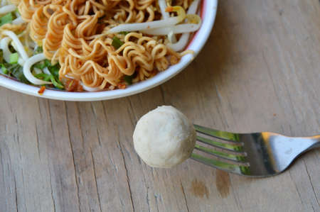 stab: pork ball stab in fork and noodle on dish