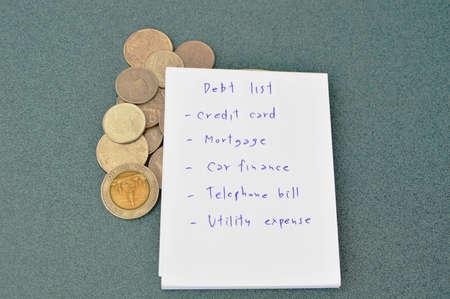 penniless: debt list and Thai money on table