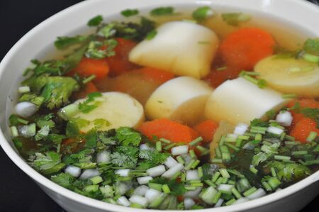 digest: egg tofu and carrot chicken soup topping chop spring onion in bowl Stock Photo