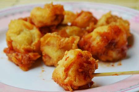 fish ball: deep fried fish ball dressing chili sauce and wooden stick Stock Photo