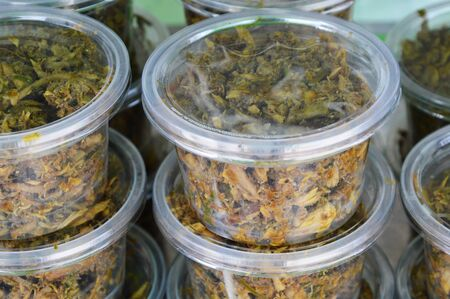 local supply: dried mackerel chili paste in plastic cup for sale Stock Photo