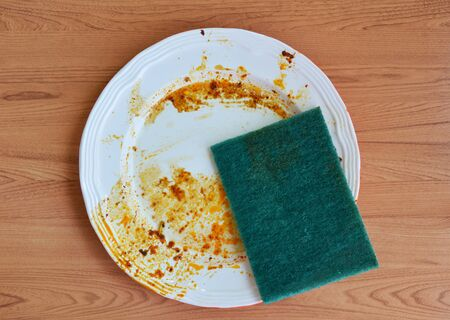 purely: green scrub sponge purely to food stain on white dish Stock Photo