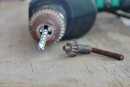 electric drill: electric drill and chuck key on wooden board