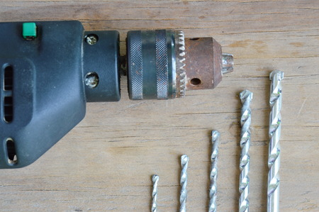 electric drill: electric drill and different size of bit on wooden board