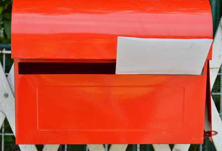 red post box: white envelope in red post box on home fence