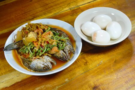 snake head fish: deep fried striped snake head fish in mixed hot and sour soup eat with boiled egg