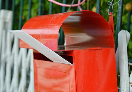 red post box: letter in red post box on home fence Stock Photo