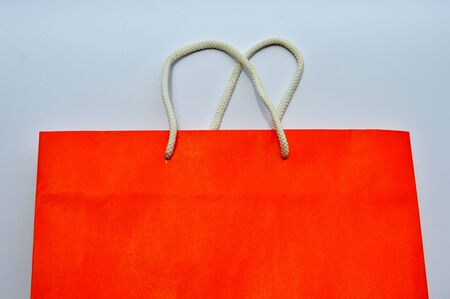 degradation: orange paper bag and white nylon rope handle