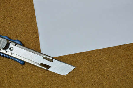 notice: cutter and paper on wooden notice board