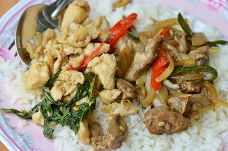 entrails: spicy stir fried chicken meat and entrails with basil leaf on rice Stock Photo