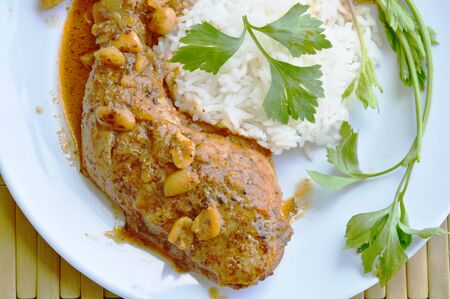 sweet and savoury: chicken leg spicy and sweet curry and plain rice on plate Stock Photo