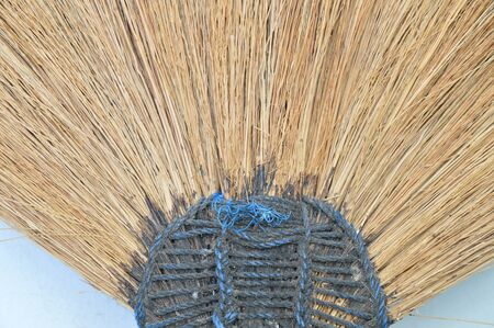 broom handle: broom grass lean on old white building wall Stock Photo
